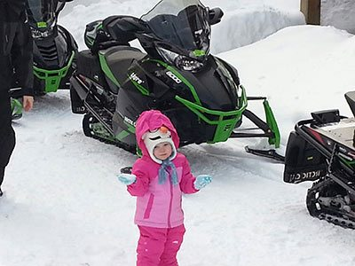 A young girl wearing a bright pink snowsuit stands in the snow and smiles.