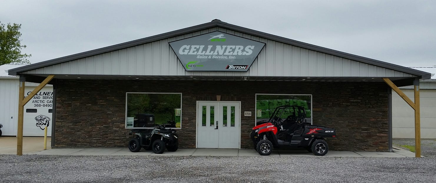 The dealership's storefront features a blue ATV and a red UTV parked in front.