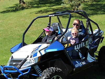 Current owners, Brian and Becca Gellner, ride with their daughter in a blue and white UTV.