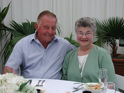 Fred and Mary Gellner smile at a dinner table.