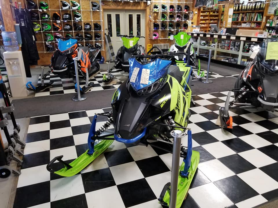 Bright snowmobiles line the dealership's showroom floor.